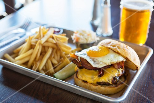 A cheeseburger with bacon, a fried egg and chips