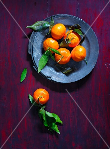 Clementines with leaves on a plate