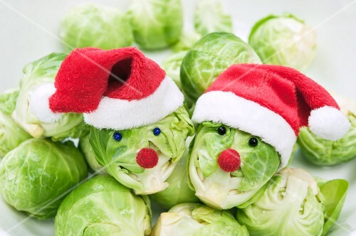 Two Brussels sprouts with faces wearing Christmas hats