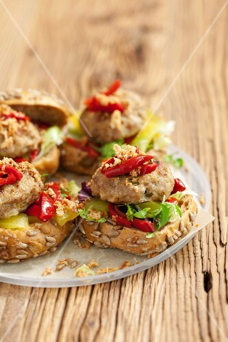Burgers topped with marinated peppers and gherkins
