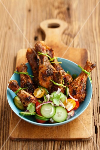 Spicy roast chicken legs with a vegetables salad