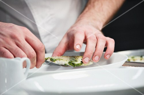 A chef putting together a fish dish on a plate