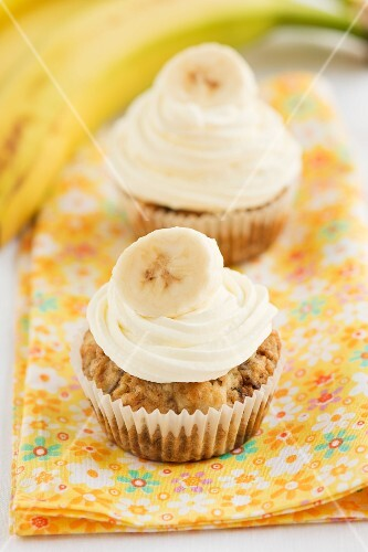 Two banana cupcakes on a floral cloth