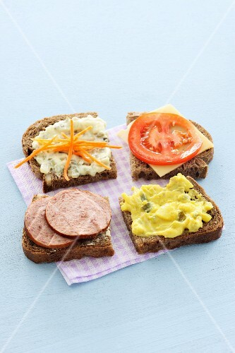 Four slices of wholemeal bread with various toppings