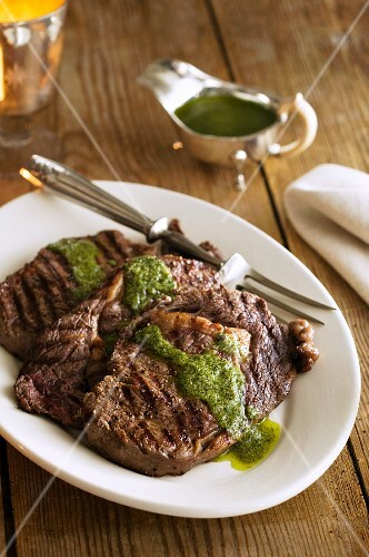 Grilled steaks with herb sauce