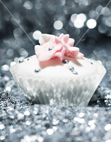 A festive cupcake decorated with silver pearls and sugar flowers