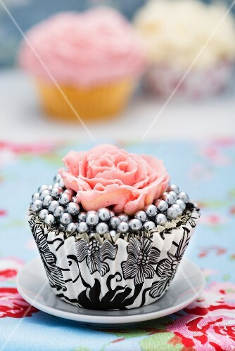 A cupcake decorated with silver pearls and a sugar rose