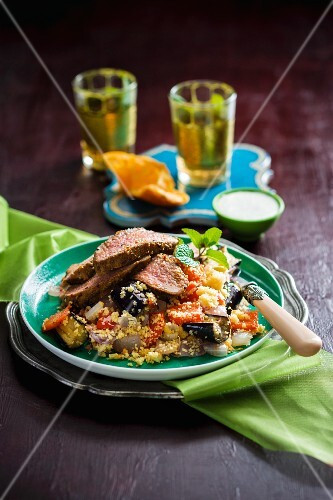Grilled lamb on a bed of couscous with fried vegetables