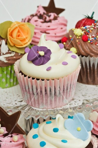 Various cupcakes decorated with sugar flowers, chocolate stars and sugar pearls