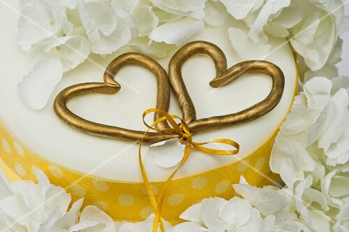 A wedding cake with two golden love hearts tied with a bow (close-up)