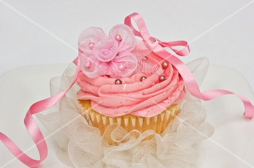 A pink cupcake with chiffon flowers and a bow