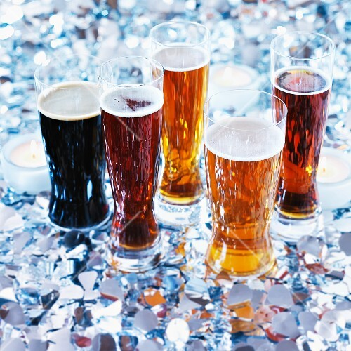 Various glasses of beer with tealights