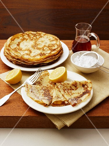 Crepes with lemon, icing sugar and maple syrup
