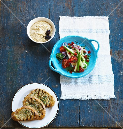 A Greek salad with a dip and a toasted bread