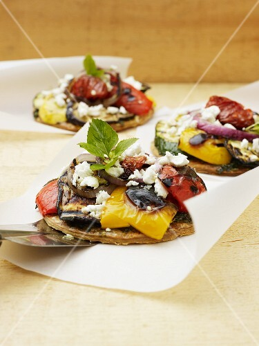 Mini pizzas topped with ratatouille and goat's cheese