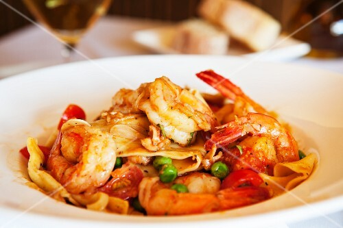 Pasta with fried prawns, tomatoes and peas