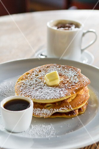 A stack of pancakes with sugar, butter and coffee