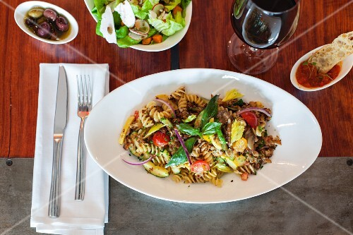 Fusilli with vegetables, salad and red wine
