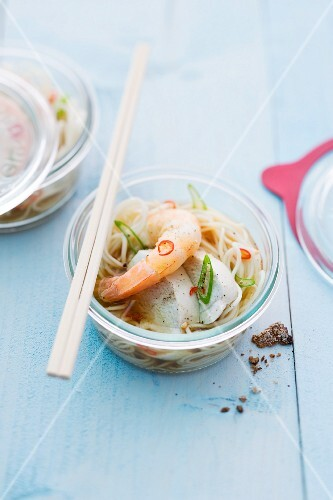 Oriental noodle soup with prawns and chicken cooked in a jar