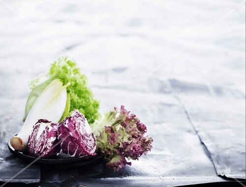 Various types of lettuce on a black plate