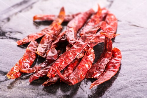 Dried chilli peppers on a slate surface