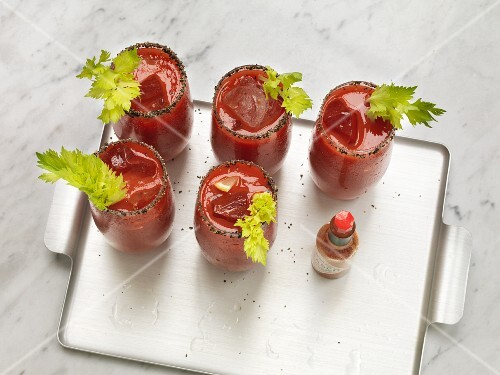 Five Bloody Marys garnished with celery on a tray