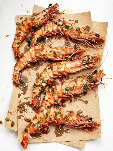King prawns with herbs on brown paper