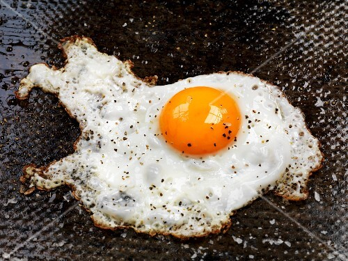 A fried egg with ground black pepper