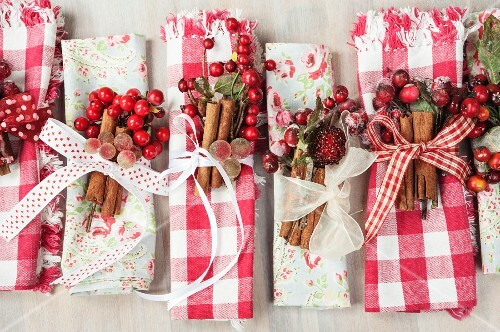 Hand-crafted, gingham and floral napkins decorated for Christmas with ribbons, berries and cinnamon sticks