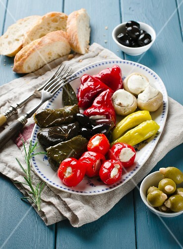 An appetiser platter with stuffed vine leaves and vegetables