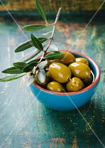 A bowl of marinated olives with an olive sprig
