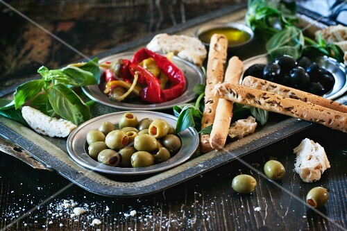 A selection of antipasti, olives and peppers with bread sticks and basil on a tray