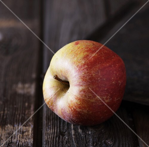 A red apple on a rustic wooden table