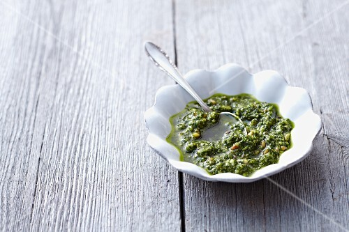 A bowl of pesto with a spoon