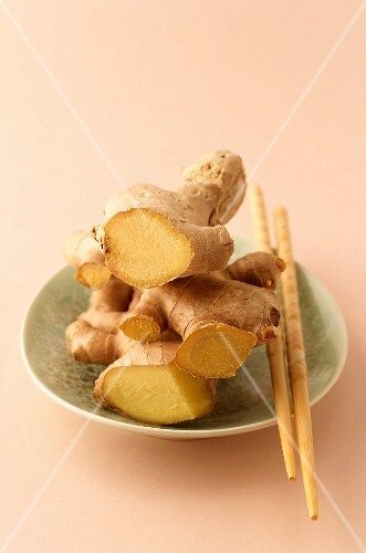 A bowl of fresh ginger with chopsticks