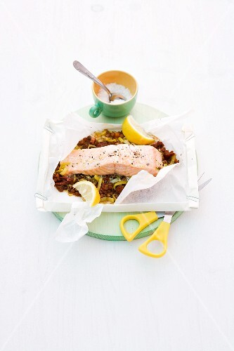 Steamed salmon on a lentil medley in baking paper