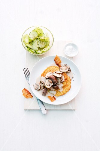Potato cakes with mushrooms, bacon and cucumber salad