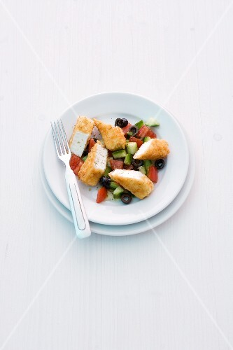 Breaded feta sticks on a cucumber and tomato salad