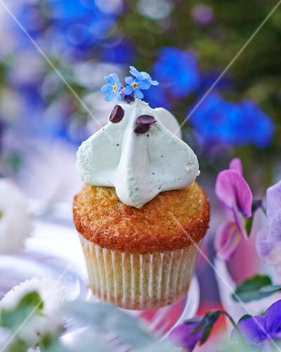 A cupcake topped with cream and forget-me-nots