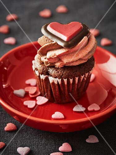 A chocolate cupcake topped with buttercream and decorated with a chocolate heart for Valentine's Day