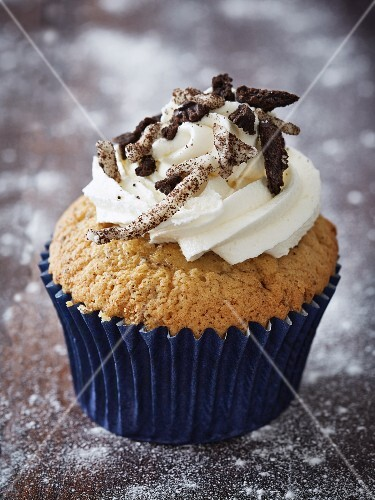 A cupcake topped with buttercream and chocolate biscuits