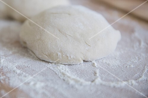 Pizza dough on a floured wooden board