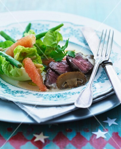 Roast beef with a mushroom sauce served with a green salad with beans and pomegranate