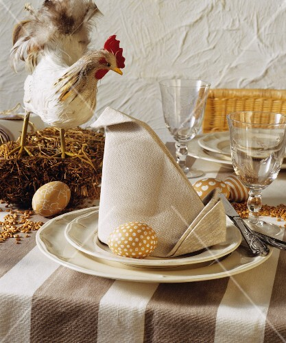 A table laid for Easter decorated with a chicken and painted eggs