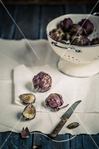 Artichokes, whole and halved, in a colander and on a cloth