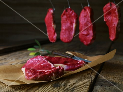 Various beef steaks (on paper and hung up)