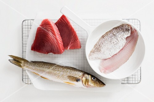 Various types of fish for frying, some in a pan