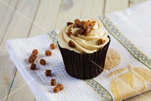 A caramel cupcake decorated with toffee pieces