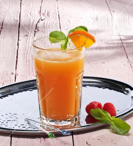 A glass of orange and raspberry lemonade