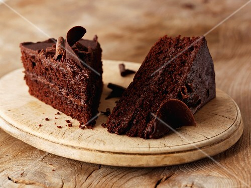 Two slices of chocolate cake on a wooden plate